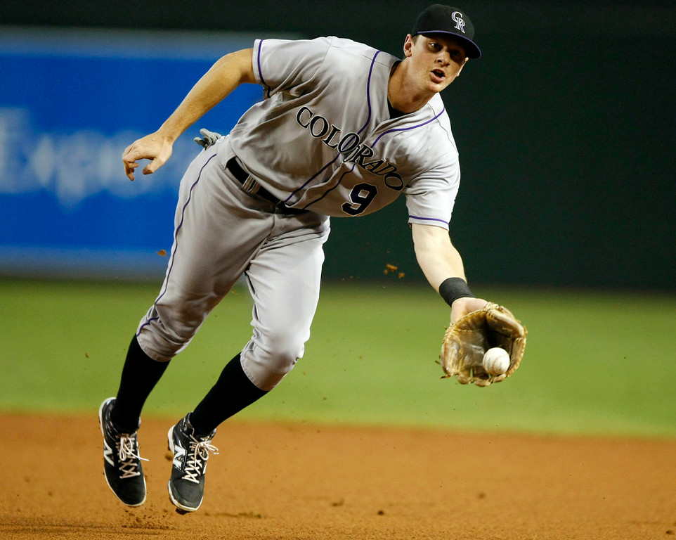 . Colorado Rockies second baseman DJ LeMahieu flips the ball to first base for the out against the Arizona Diamondbacks in the second inning during a baseball game, Sunday, Aug. 10, 2014, in Phoenix. (AP Photo/Rick Scuteri)