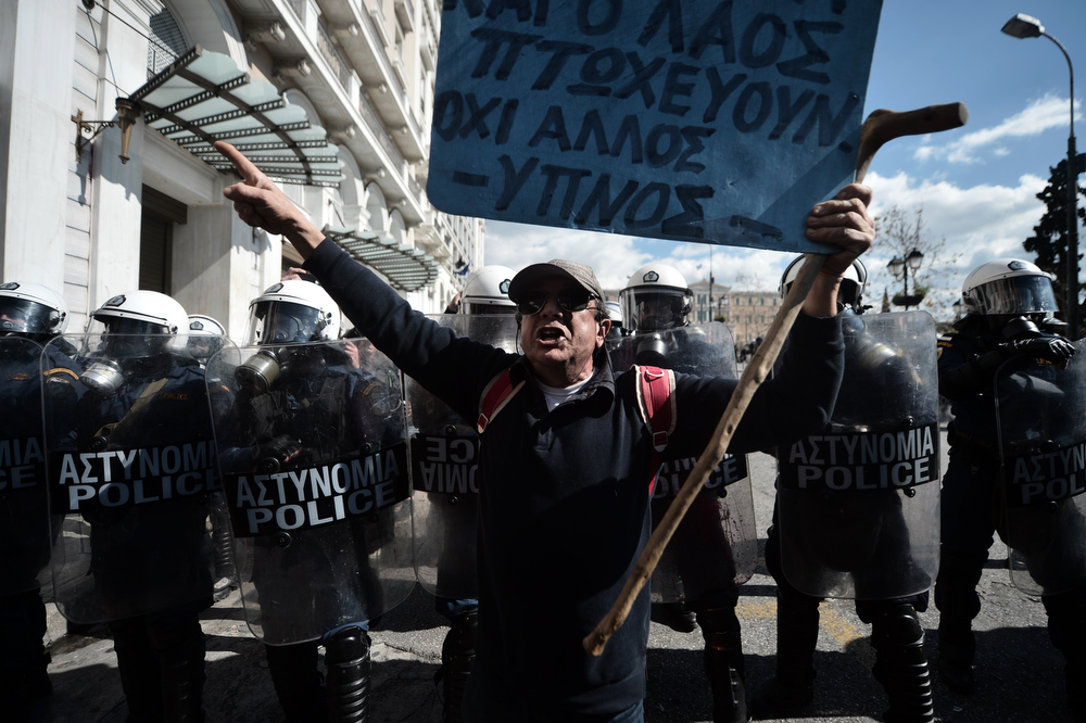 . A demonstrator shouts slogans in front of riot police during a 24-hour general strike in Athens on February 20, 2013.  Greece was hit by a new strike on February 20 called by leading unions against unrelenting austerity in the recession-weary nation ahead of an audit by international creditors, disrupting flights, ferries and hospital services. The strike -- the first general work stoppage in debt-crippled Greece this year -- has forced airport authorities to scrap or reschedule dozens of flights while hospitals were operating on reduced staffing. ARIS MESSINIS/AFP/Getty Images