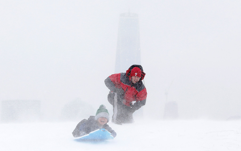 . Rick Caso, center, watches as his son Andrew sleds down a hill, with One World Trade Center obscured in the background, at Liberty State Park, Monday, Jan. 26, 2015, in Jersey City, N.J.  The Philadelphia-to-Boston corridor of more than 35 million people began shutting down as a monster storm, that could unload a paralyzing 1 to 3 feet of snow, moved through the northeast. (AP Photo/Julio Cortez)