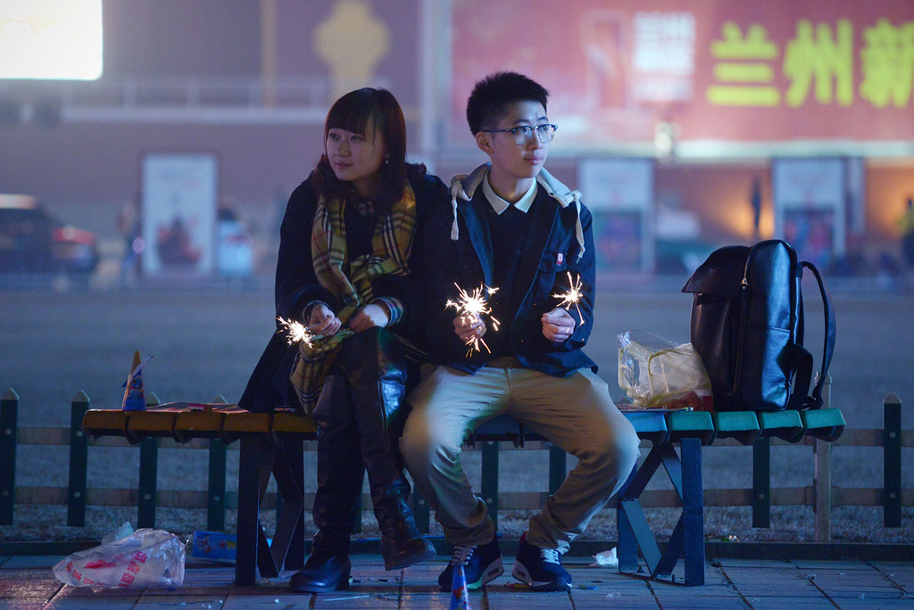 . A couple hold fireworks as they sit together on a bench in Lanzhou, northwest China\'s Gansu province, on January 30, 2014, on the eve of the Lunar New Year.    AFP PHOTO / WANG  ZHAO/AFP/Getty Images