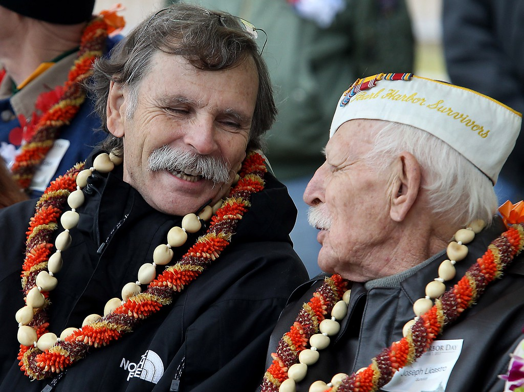 . Pearl Harbor survivor Joseph Licastro sits with his son Joe Licastro Jr., during the annual Pearl Harbor Day Remembrance Ceremony Saturday, Dec. 7, 2013 in Bakersfield, Calif., at the Union Cemetery. (AP Photo/The Bakersfield Californian, Casey Christie)
