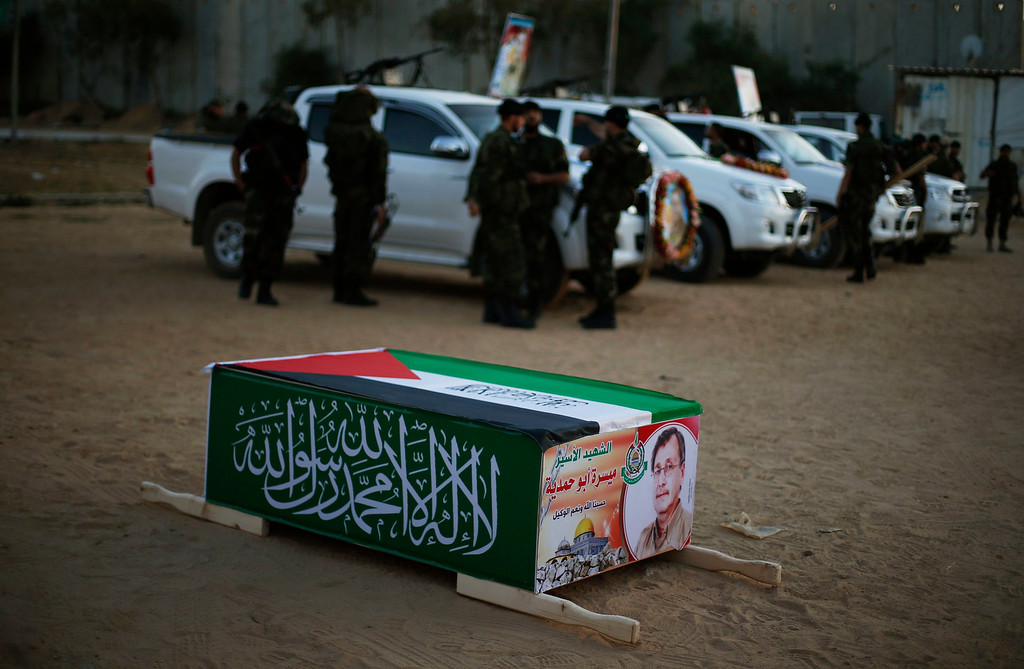 . Hamas militants stand next to a mock coffin of Maysara Abu Hamdeya before a protest in the northern Gaza Strip April 2, 2013. Israeli prison guards fired tear gas to quell disturbances by Palestinian inmates on Tuesday after a prisoner serving a life sentence over an attempt to bomb an Israeli cafe died of cancer. Maysara Abu Hamdeya\'s death threatened to raise tensions in the Israeli-occupied West Bank, where Palestinians, who view jailed brethren as heroes in a fight for statehood, have held several protests in recent weeks in support of prisoners. REUTERS/Suhaib Salem