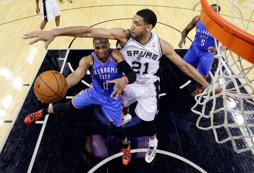 . Oklahoma City Thunder\'s Russell Westbrook (0) is defended by San Antonio Spurs\' Tim Duncan (21) as he drives to the basket during the first half of Game 1 of a Western Conference finals NBA basketball playoff series, Monday, May 19, 2014, in San Antonio. San Antonio won 122-105. (AP Photo/Eric Gay)