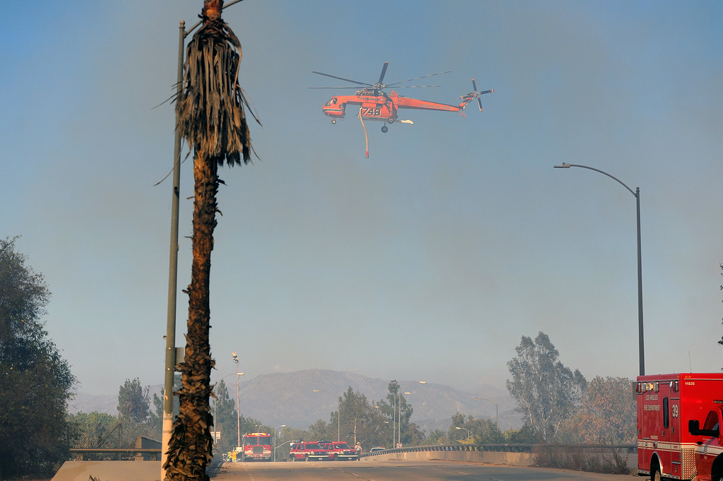 . A helicopter flies over Burbank Boulevard during a brushfire in the Sepúlveda Basin, Friday, August 22, 2014. (Photo by Michael Owen Baker/Los Angeles Daily News)