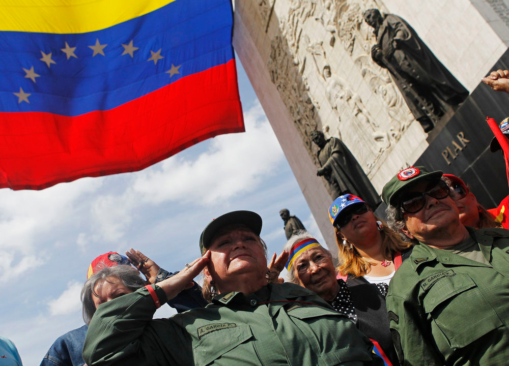 . Supporters of Venezuela\'s late President Hugo Chavez salute under the Monument to the Founding Fathers as they line up to view his body in state at the Military Academy in Caracas on March 7, 2013. Venezuelans flocked to pay tribute to Chavez two days after he died of cancer. REUTERS/Mariana Bazo