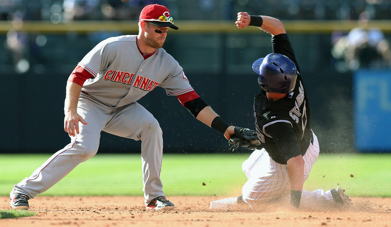 . Cincinnati Reds shortstop Zack Cozart, left, applies a late tag to Colorado Rockies\' Drew Stubbs as he steals second base in the eighth inning of the Rockies\' 10-9 victory in a baseball game in Denver on Sunday, Aug. 17, 2014. (AP Photo/David Zalubowski)