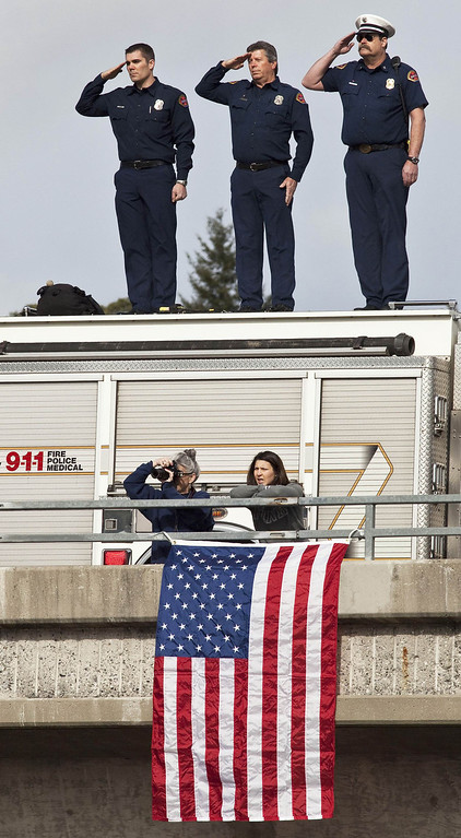 . Santa Clara firefighters (L-R) David Sosine, Bruce Ingle, and Dave Riggert salute from an overpass as the motorcade procession honoring Santa Cruz Police Department officers\' Loran Baker and Elizabeth Butler travels to the officers memorial services in San Jose, California March 7, 2013. The two officers were killed in the line of duty February 26 while arriving at the home of a suspect they were to question.  REUTERS/Mark Avery  (UNITED STATES - Tags: CRIME LAW)