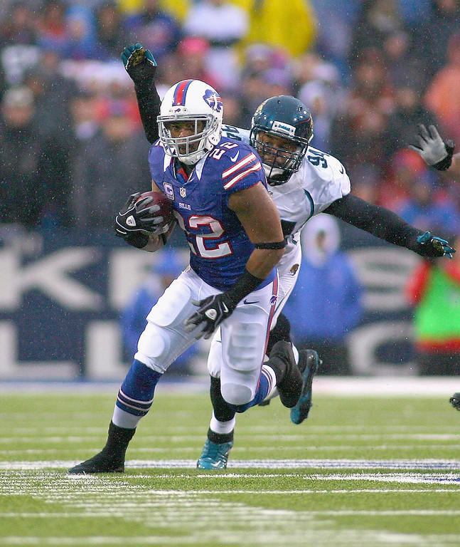. Fred Jackson #22 of the Buffalo Bills runs ahead of Jeremy Mincey #94 of the Jacksonville Jaguars at Ralph Wilson Stadium on December 2, 2012 in Orchard Park, New York.  (Photo by Rick Stewart/Getty Images)