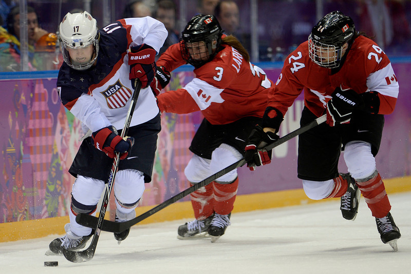 . Jocelyne Larocque (3) of the Canada and Natalie Spooner (24) defend Jocelyne Lamoureaux (17) of the U.S.A. during the third period of the women\'s gold medal ice hockey game. Sochi 2014 Winter Olympics on Thursday, February 20, 2014 at Bolshoy Ice Arena. (Photo by AAron Ontiveroz/ The Denver Post)