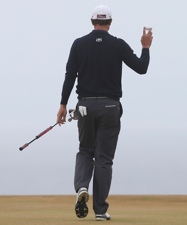 . Adam Scott of Australia holds up his ball after putting on the 11th green during the final round of the British Open Golf Championship at Muirfield, Scotland, Sunday July 21, 2013. (AP Photo/Scott Heppell)