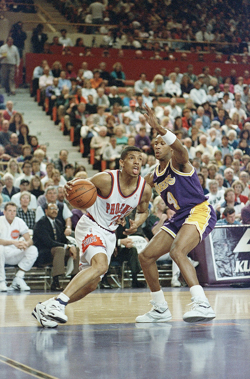 . Phoenix Suns Kevin Johnson drives past Los Angeles Lakers Byron Scott during action in their NBA game on Monday, Feb. 3, 1992 in Phoneix. (AP Photo/Jeff Robbins)