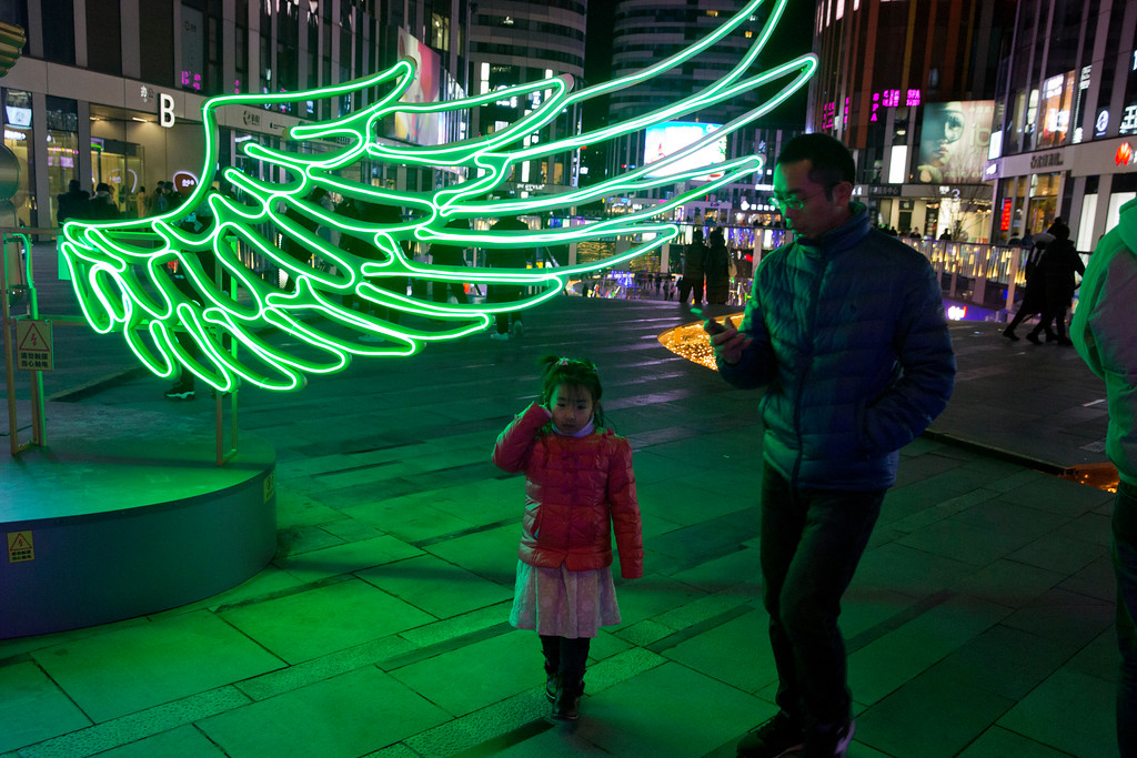 . A child walks past a neon light display at a shopping mall during Christmas eve in Beijing, China, Sunday, Dec. 24, 2017. Retailers looking for a year end boost in sales find an opportunity in the younger generation\'s willingness to embrace the western gift giving tradition of Christmas which is not customarily celebrated in China (AP Photo/Ng Han Guan)