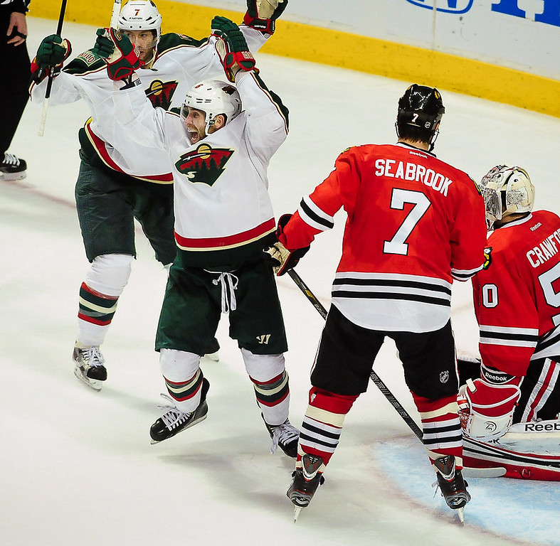 . Minnesota Wild left wing Jason Zucker, middle, and center Matt Cullen, back left, celebrate their team\'s second goal during the third period. At right is Chicago Blackhawks defenseman Brent Seabrook and goalie Corey Crawford.  (Pioneer Press: Ben Garvin)