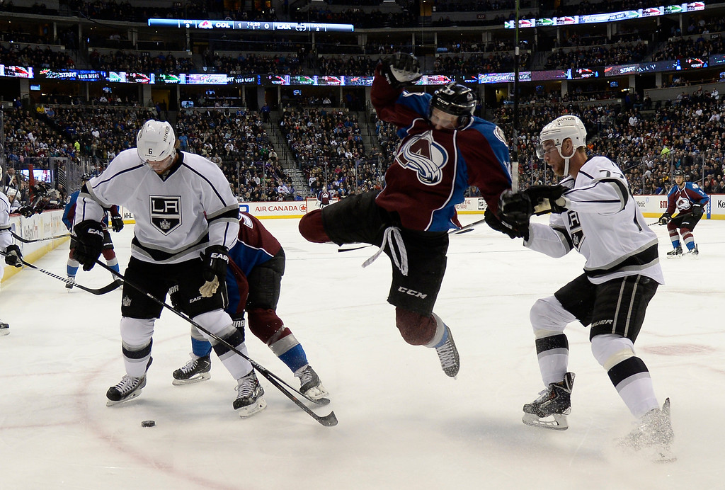 . DENVER, CO - FEBRUARY 18: Colorado Avalanche center Nathan MacKinnon (29) gets knocked off his skates by Los Angeles Kings center Jeff Carter (77) as Los Angeles Kings defenseman Jake Muzzin (6) and Colorado Avalanche center Ryan O\'Reilly (90) battle for the puck during the first period February 18, 2015 at Pepsi Center. (Photo By John Leyba/The Denver Post)