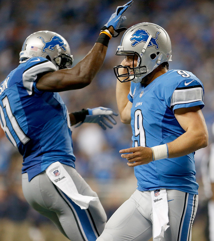 . DETROIT, MI - SEPTEMBER 29:  Calvin Johnson #81 and Matthew Stafford #9 of the Detroit Lions celebrate a touchdown against the Chicago Bears at Ford Field on September 29, 2013 in Detroit, Michigan. (Photo by Gregory Shamus/Getty Images)