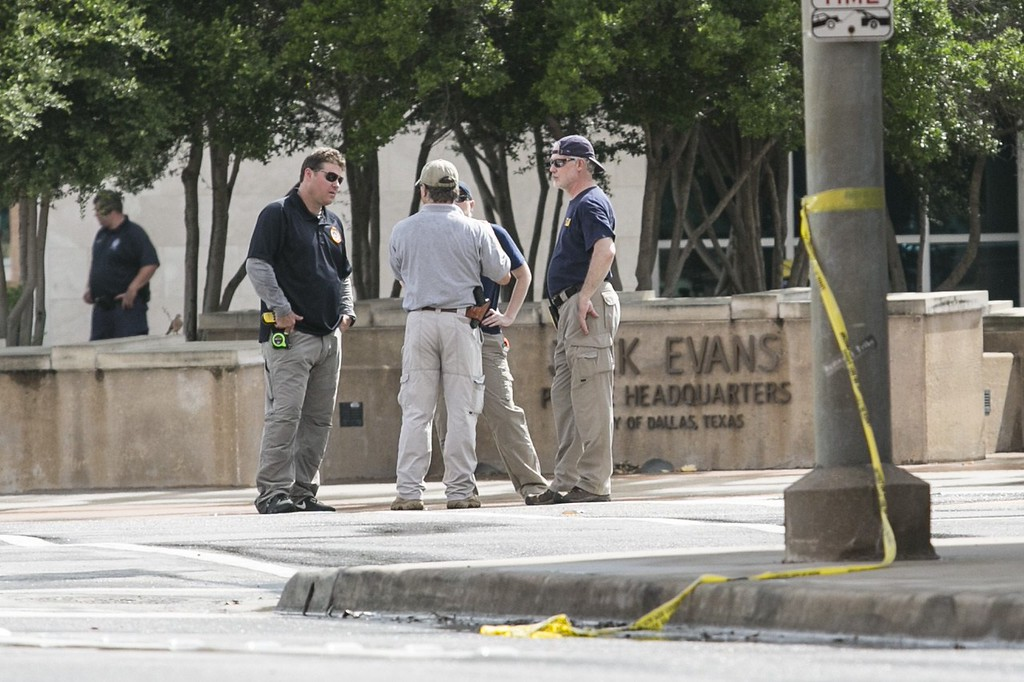 . Members of law enforcement gather outside the Dallas police department following the early morning shooting on  June 13, 2015 in Dallas, Texas.  Snipers shot and presumably killed a suspect in a standoff by the Dallas police headquarters in Texas, officials said Saturday, adding there were no known links to terrorism. A bomb disposal robot was inspecting an armored van after SWAT team snipers shot through the front of the windshield of the vehicle and struck the suspect, Police Chief David Brown told reporters. AFP PHOTO/LAURA  BUCKMAN/AFP/Getty Images