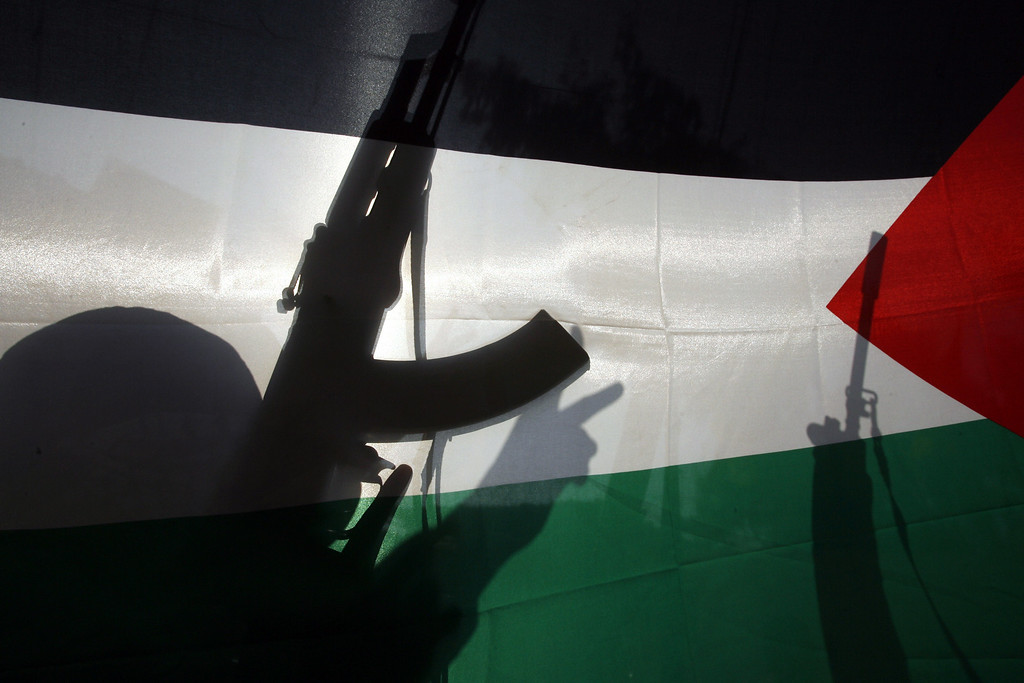 . The shadow of an armed member of the Popular Front for the liberation od Palestine (PFLP) flashing the sign for victory is seen behind a Palestinian flag at the Palestinian refugee camp of Ain El-Helweh, near the southern Lebanese coastal city of Sidon, as they celebrate the attack by two Palestinians on a synagogue in Jerusalem on November 18, 2014. Two Palestinians armed with a gun and meat cleavers burst into a Jerusalem synagogue and killed four Israelis before being shot dead in the city\'s bloodiest attack in years. AFP PHOTO / MAHMOUD ZAYYAT/AFP/Getty Images