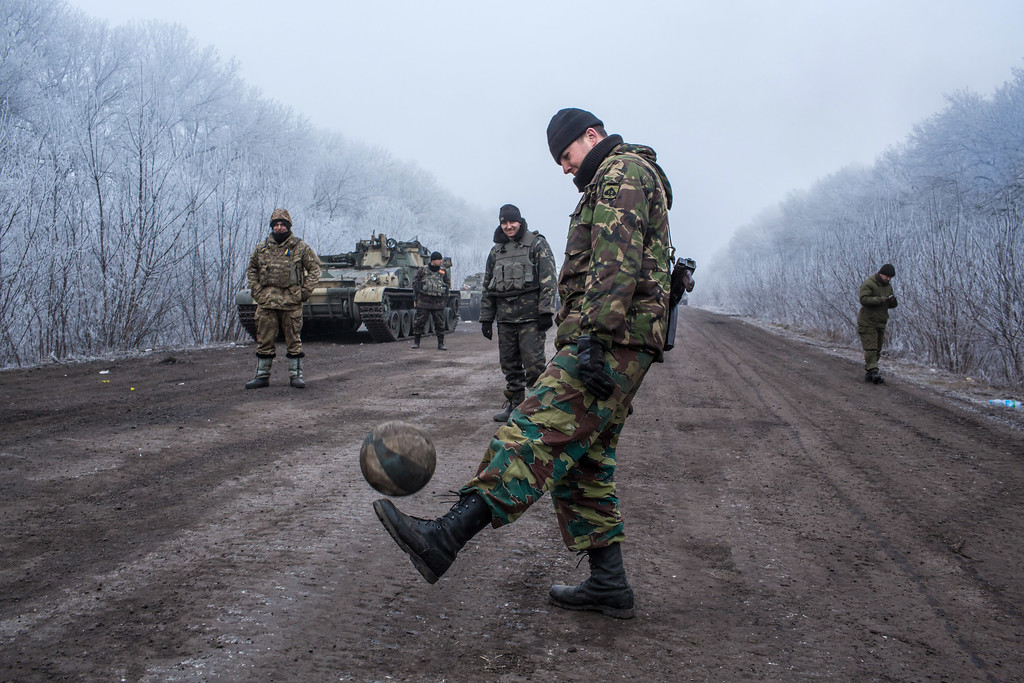 . ARTEMIVSK, UKRAINE - FEBRUARY 15: Ukrainian soldiers play football on the road leading to the embattled town of Debaltseve on February 15, 2015 outside Artemivsk, Ukraine. A ceasefire scheduled to go into effect at midnight was reportedly observed along most of the front, save for near the embattled town of Debaltseve. (Photo by Brendan Hoffman/Getty Images)