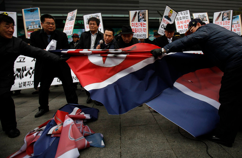 . Activists from an anti-North Korea civic group try to tear a North Korea flag during a rally against North Korea\'s nuclear test near the U.S. embassy in central Seoul February 12, 2013. North Korea conducted its third nuclear test on Tuesday in defiance of U.N. resolutions, angering the United States and Japan and prompting its only major ally, China, to call for calm.   REUTERS/Kim Hong-Ji