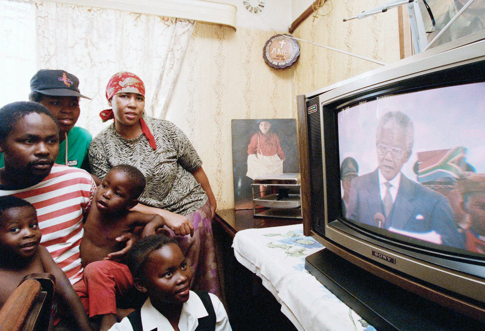 Description of . Members of the Moledi family in Soweto, South Africa watch a live broadcast of the inauguration of President-elect Nelson Mandela in Pretoria, May 10, 1994. Mandela was sworn in as South Africa's first black president. (AP Photo/Joao Silva)