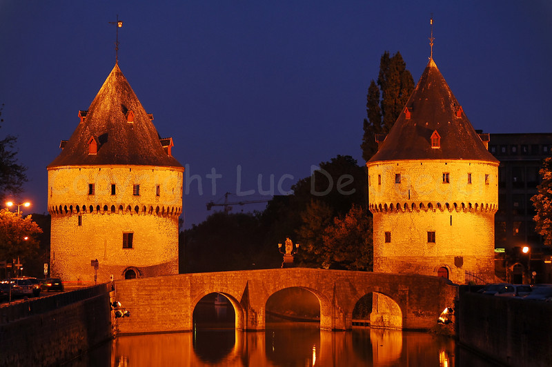 The two near-identical medieval Broel Towers (Broeltorens) in Courtrai (Kortrijk), Belgium, with the bridge in between that spans the river Lys (Leie). The towers are called the Speyetower and the Ingelburgtower. Photo captured at dusk. The towers are built in the 14th and 15th century and are the last remaining parts of the medieval city wall around the city.