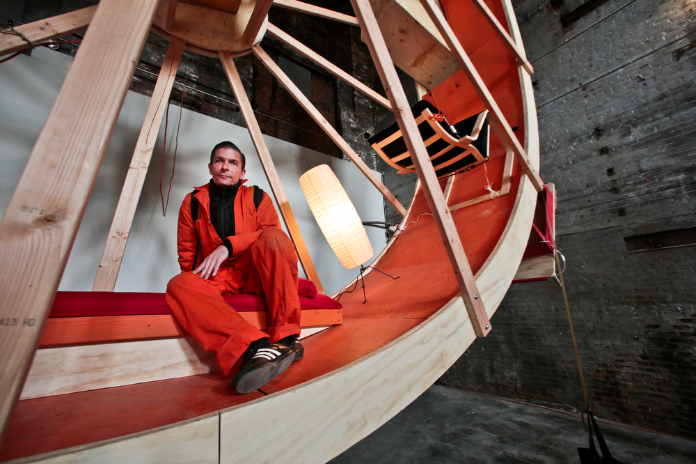 """. Alex Schweder sits inside the  performance art \""""In Orbit,\"""" a 25-foot wheel made from wood, steel, and furniture, his home for 10 days along with fellow artist Ward Shelley at the Boiler gallery in the Brooklyn borough of New York, Tuesday, March 4, 2014. They will share two living units arrayed over the hamster-wheel-like sculpture, with Shelly living on the outside and Schweder on the inside. The structure will remain on view through April 5.  (AP Photo/Bebeto Matthews)"""