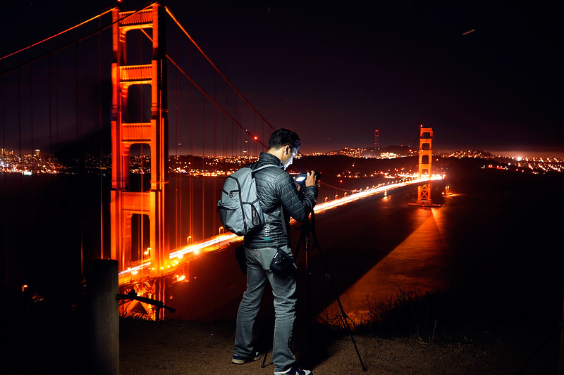 """Nov 17 '16 ~ Long exposure shot of my photog friend @ Marin Headlands.  I put the camera on a tripod with a 4 second exposure to make the car lights over the Golden Gate blurred out, simultaneously using my phone light to """"paint"""" over the subject.  He needed to stay super still over the 4 seconds to come out sharp in the end.  I did a bit of composite editing in the end, taking a couple pieces of two other similar photographs to make the bridge and city lights in the distance stand out a bit more."""