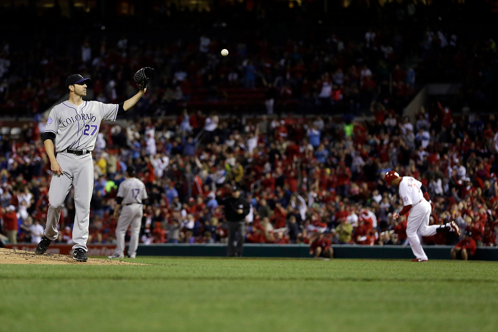 . Colorado Rockies starting pitcher Jon Garland, left, gets a new ball after giving up a solo home run to St. Louis Cardinals\' Carlos Beltran, right, during the third inning of a baseball game on Friday, May 10, 2013, in St. Louis. (AP Photo/Jeff Roberson)