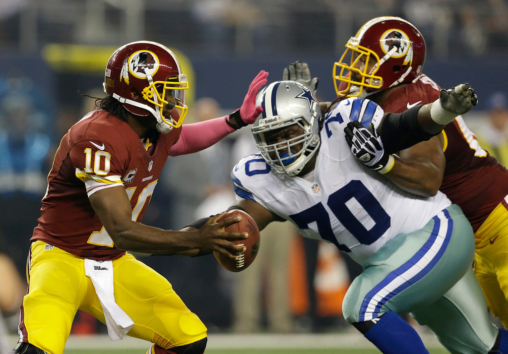 . Washington Redskins quarterback Robert Griffin III (10) guards against a rush by Dallas Cowboys defensive tackle Drake Nevis (70) in the first half of an NFL football game, Sunday, Oct. 13, 2013, in Arlington, Texas. (AP Photo/LM Otero)