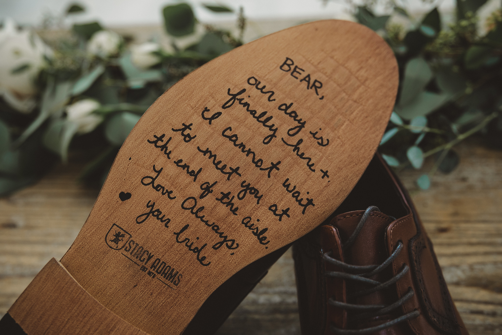 a groom's wedding shoes with a note from his bride on the sole