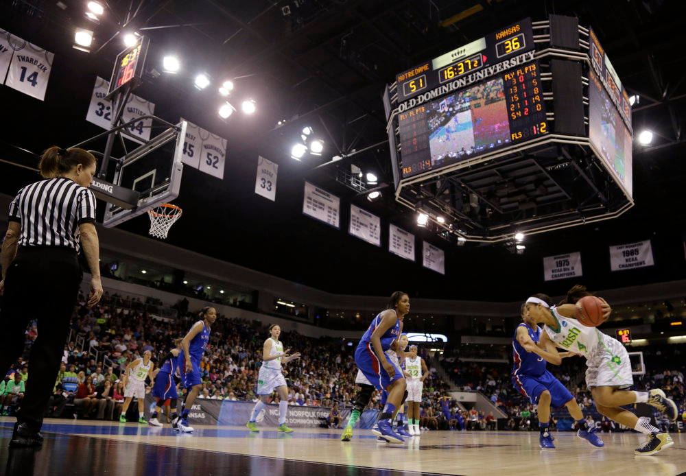 Description of . Notre Dame guard Skylar Diggins, right, drives to the basket during the second half of a regional semi-final of an NCAA college basketball tournament  Sunday March 31, 2013 in Norfolk, Va. Notre Dame won 93-63.  (AP Photo/Steve Helber)