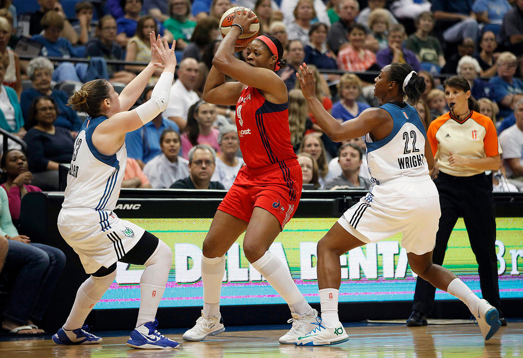 . Washington Mystics\' Kia Vaughn (9) looks for an opening to make a pass against Minnesota Lynx guards Lindsay Whalen (13) and Monica Wright (22) in the first half. (AP Photo/Stacy Bengs)