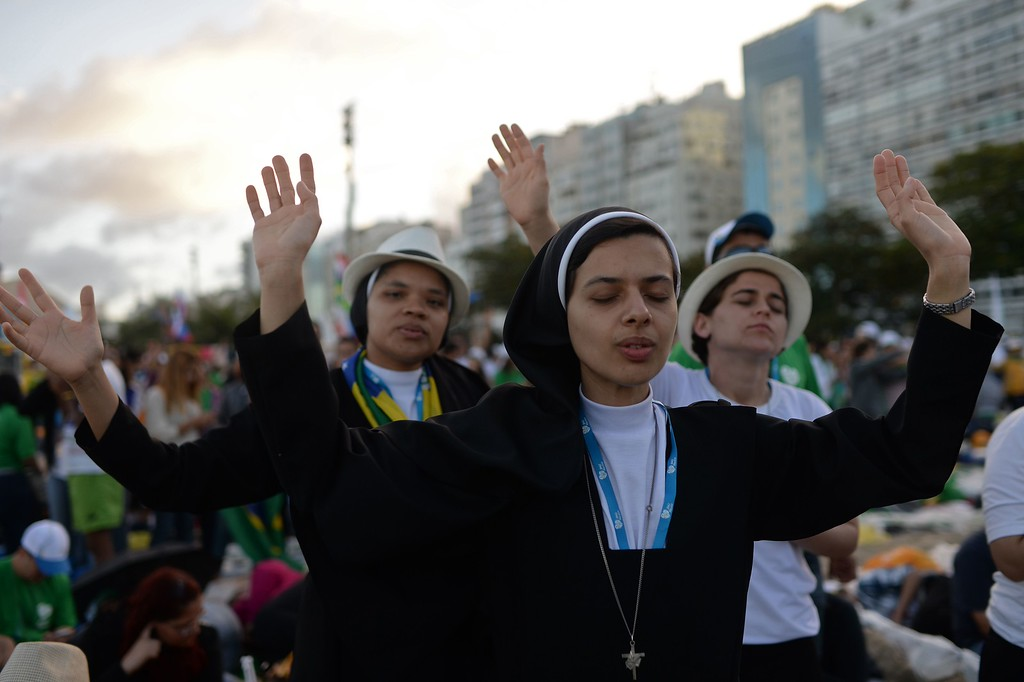 ". Nuns follow a group of artists performing on the stage before the arrival of Pope Francis for a prayer vigil with hundreds of thousands of young Catholic pilgrims attending World Youth Day (WYD), at Copacabana beach in Rio de Janeiro, on July 27, 2013. In a speech to Brazil\'s political, religious and civil society leaders earlier, Pope Francis said a ""constructive dialogue\"" was needed to confront the country\'s social turmoil, referring to the massive street protests that rocked Brazil last month to demand an end to corruption and better public services. YASUYOSHI CHIBA/AFP/Getty Images"