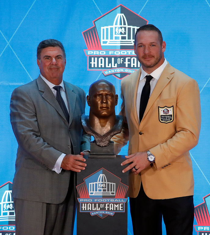 . Former NFL player Brian Urlacher, right, poses with a bust of himself and presenter, former coach with the Bears Bob Babich, during an induction ceremony at the Pro Football Hall of Fame, Saturday, Aug. 4, 2018 in Canton, Ohio. (AP Photo/Gene J. Puskar)