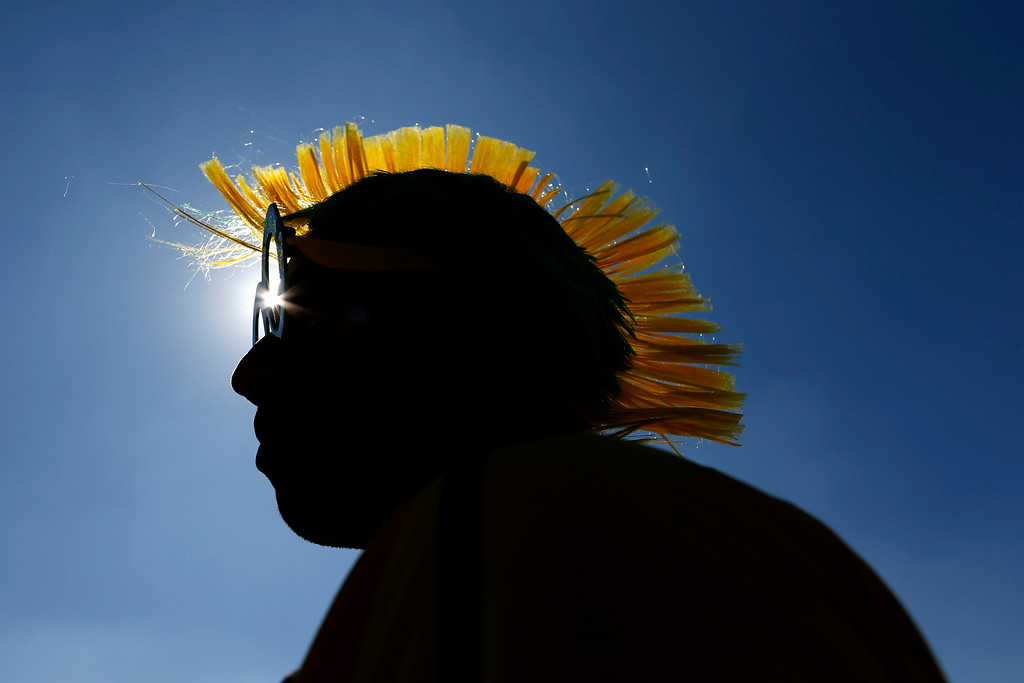 """. Brazilian Marcelo Bora, 22, and his mohawk-styled wig, are silhouetted against a blue sky as he waits to enter the Itaquerao Stadium to watch the World Cup opening match, between Brazil and Croatia of group A, in Sao Paulo, Brazil, Thursday, June 12, 2014. Thursday is a holiday in Sao Paulo and everybody is celebrating the start of the international soccer tournament. Fans dressed in yellow and green greeted each other, often yelling, \""""Vai Brazil!\""""  (AP Photo/Julio Cortez)"""