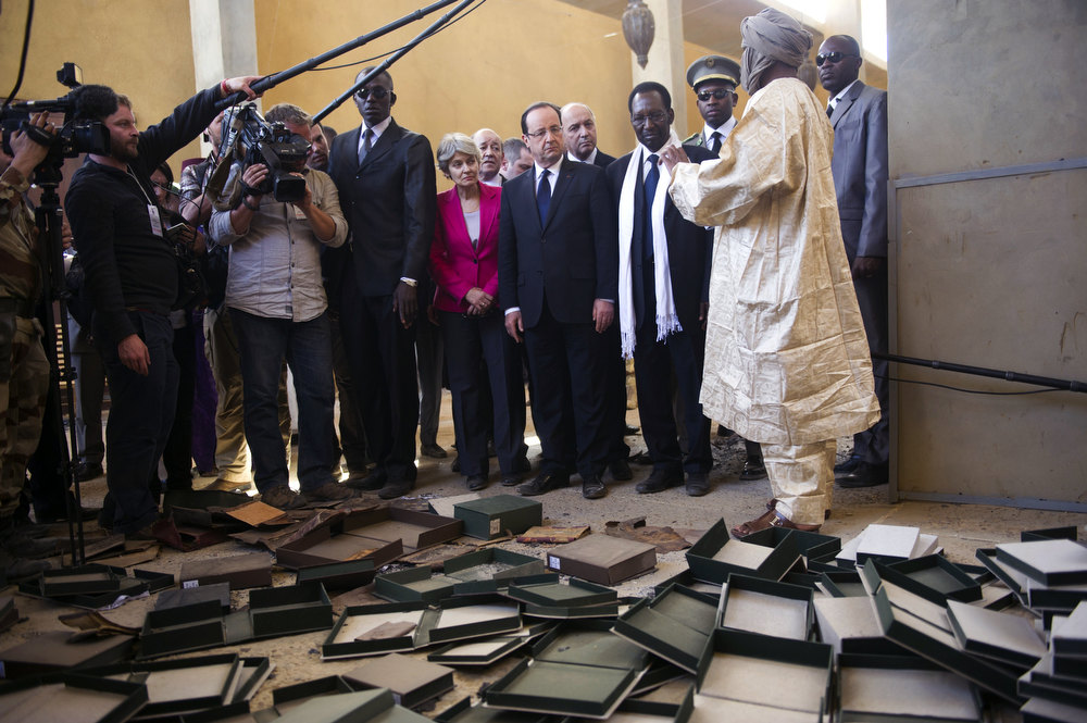 Description of . France\'s President Francois Hollande (5thR) flanked by Mali\'s interim president Dioncounda Traore (3dR), French Foreign Affairs minister Laurent Fabius (R) and UNESCO general director Irina Bokova from Bulgaria (C)  visit the archives where documents were burnt in Timbuktu, the second step of his one-day visit in Mali, on February 2, 2013. Islamists had torched the building housing priceless ancient manuscripts as they fled the town. FRED DUFOUR/AFP/Getty Images