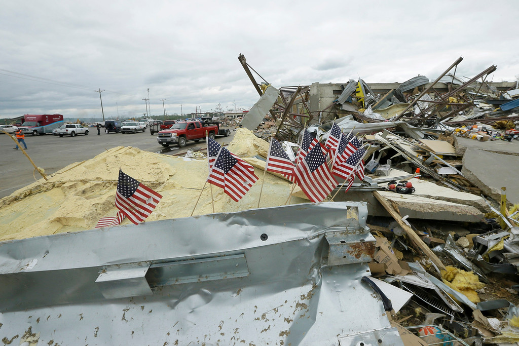. Small flags fly at the destroyed Vilonia Shopping enter in Vilonia, Ark., Wednesday, April 30, 2014. A tornado struck the town late Sunday.  Along stretches of damaged houses, volunteers with chain saws cleared trees from across homes, driveways and streets.  (AP Photo/Danny Johnston)