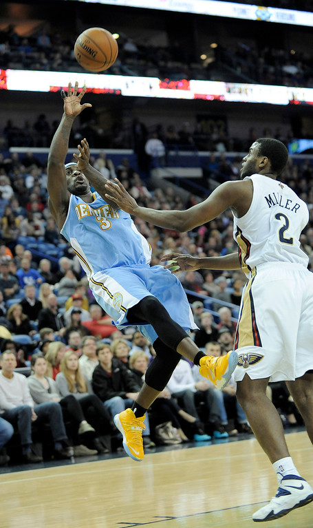 . Denver Nuggets guard Ty Lawson (3) shoots over New Orleans Pelicans forward Darius Miller (2) during the first half of an NBA basketball game in New Orleans, Friday, Dec. 27, 2013.  (AP Photo/Stacy Revere)