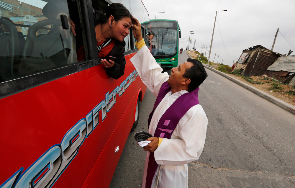 Description of . Catholic priest Jesus Cardona places ashes in the shape of a cross on the forehead of a woman traveling by bus in Bogota, Colombia, Wednesday, March 5, 2014. Cardona, 39, walked through the neighborhood of his church the morning of Ash Wednesday to offer blessings to commuters on the start of the Lent, a season of prayer and fasting before Easter. (AP Photo/Fernando Vergara)
