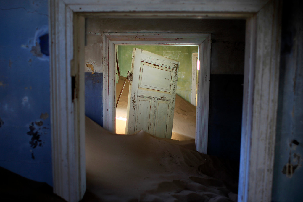 . In this July 23, 2013 photo, sand fills an abandoned house in Kolmanskop, Namibia. Kolmanskop, was a diamond mining town south of Namibia, build in 1908 and deserted in 1956. SInce then, the desert slowly reclaims its territory, with sand invading the buildings where 350 German colonists and more than 800 local workers lived during its hay-days of the 1920s. (AP Photo/Jerome Delay)