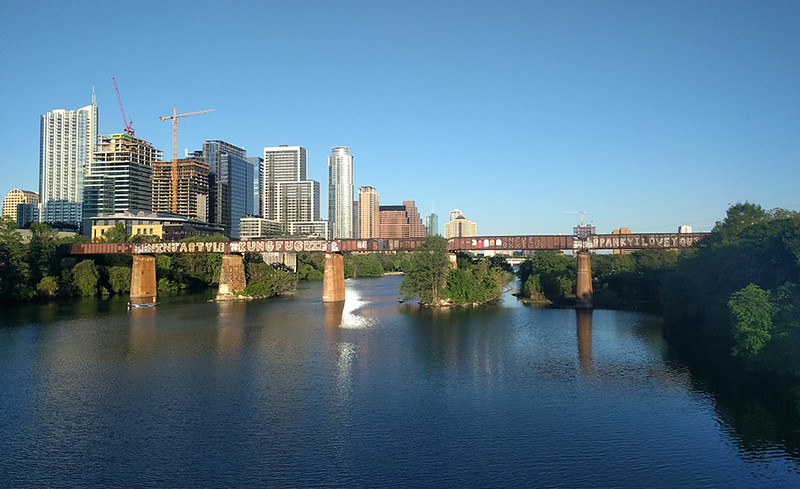 skyline withbridge crossing a river in forefront