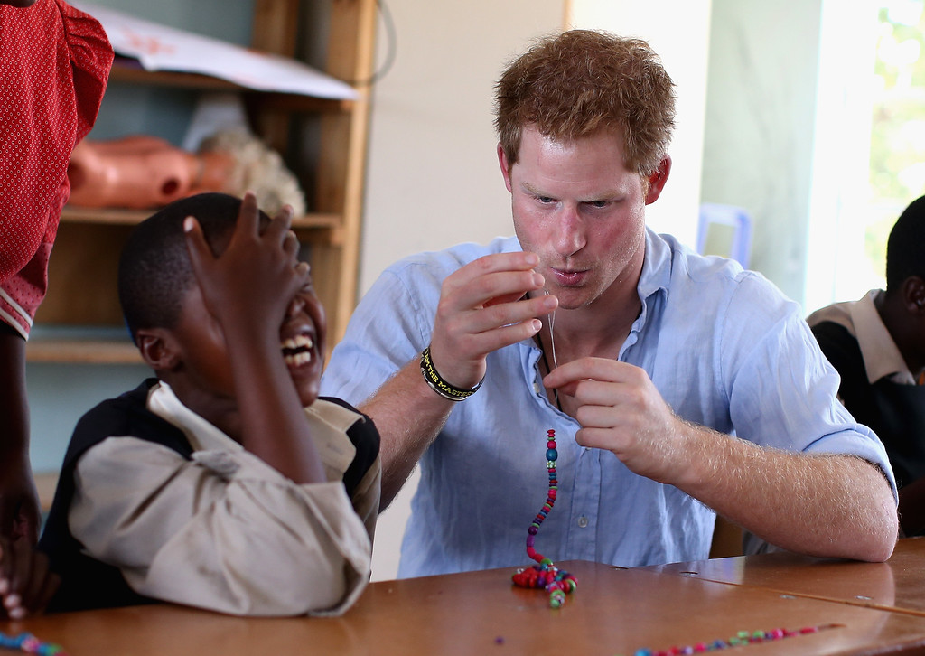 . Prince Harry makes bead necklaces during a visit to the Thuso Centre for children living with multiple disabilities on December 7, 2014 in Bute-Bute, Lesotho. (Photo by Chris Jackson/Getty Images for Sentebale)