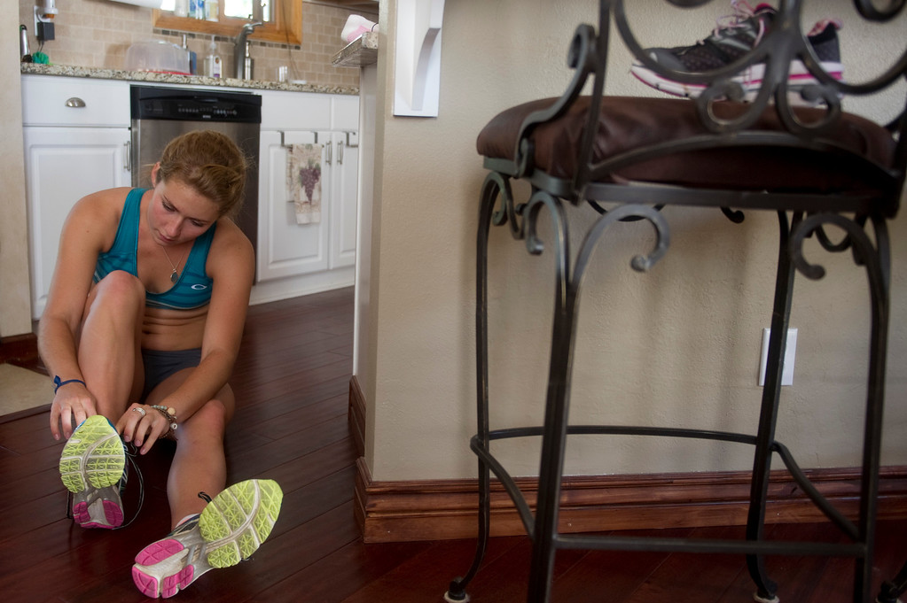 . Olympic downhill skier Mikaela Shiffrin puts on her shoes in her kitchen before running four miles uphill as part of her training regime for this year\'s Winter Olympics, in Beaver Creek Co. on July 15, 2013. (Photo By Grant Hindsley/The Denver Post)