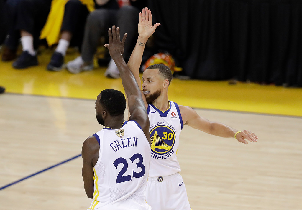 . Golden State Warriors guard Stephen Curry (30) celebrates with forward Draymond Green (23) during overtime of Game 1 of basketball\'s NBA Finals against the Cleveland Cavaliers in Oakland, Calif., Thursday, May 31, 2018. The Warriors won 124-114. (AP Photo/Marcio Jose Sanchez)