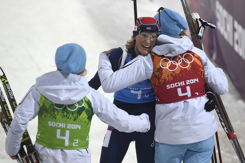 . Bronze medalist Norway\'s Tora Berger  (C) is congratulated by team mates Tiril Eckhoff (L) and Fanny Welle-Strand Horn at the finish line in the Women\'s Biathlon 4x6 km Relay at the Laura Cross-Country Ski and Biathlon Center during the Sochi Winter Olympics on February 21, 2014, in Rosa Khutor, near Sochi. (ODD ANDERSEN/AFP/Getty Images)