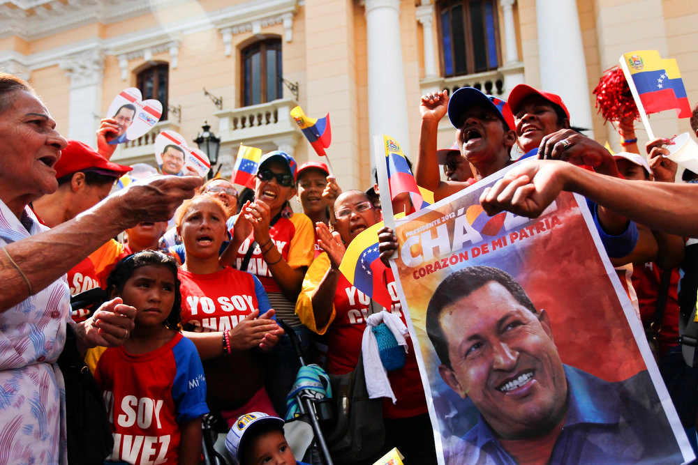 Description of . Supporters of Venezuelan President Hugo Chavez gather at Plaza Bolivar in Caracas February 18, 2013. Chavez made a surprise return from Cuba on Monday more than two months after surgery for cancer that has jeopardized his 14-year rule of the South American OPEC member. The 58-year-old socialist leader underwent a six-hour operation in Cuba on December 11 and had not been seen or heard in public until photos of him were published on Friday. REUTERS/Carlos Garcia Rawlins