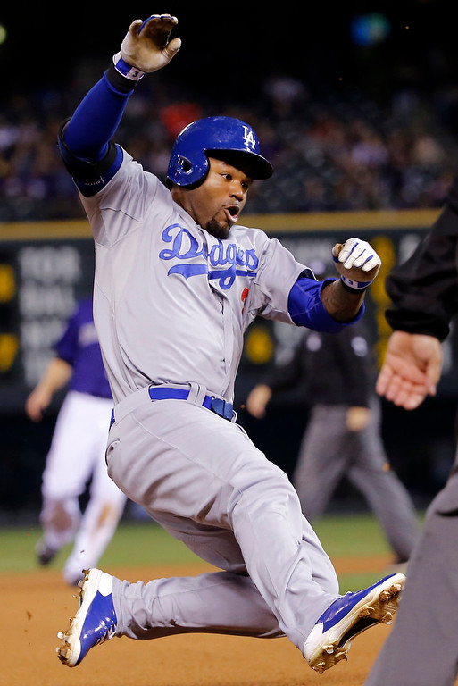 . Los Angeles Dodgers\' Carl Crawford is airborn while sliding into third on a triple against the Colorado Rockies during the fourth inning of a baseball game Monday, Sept. 15, 2014, in Denver. (AP Photo/Jack Dempsey)