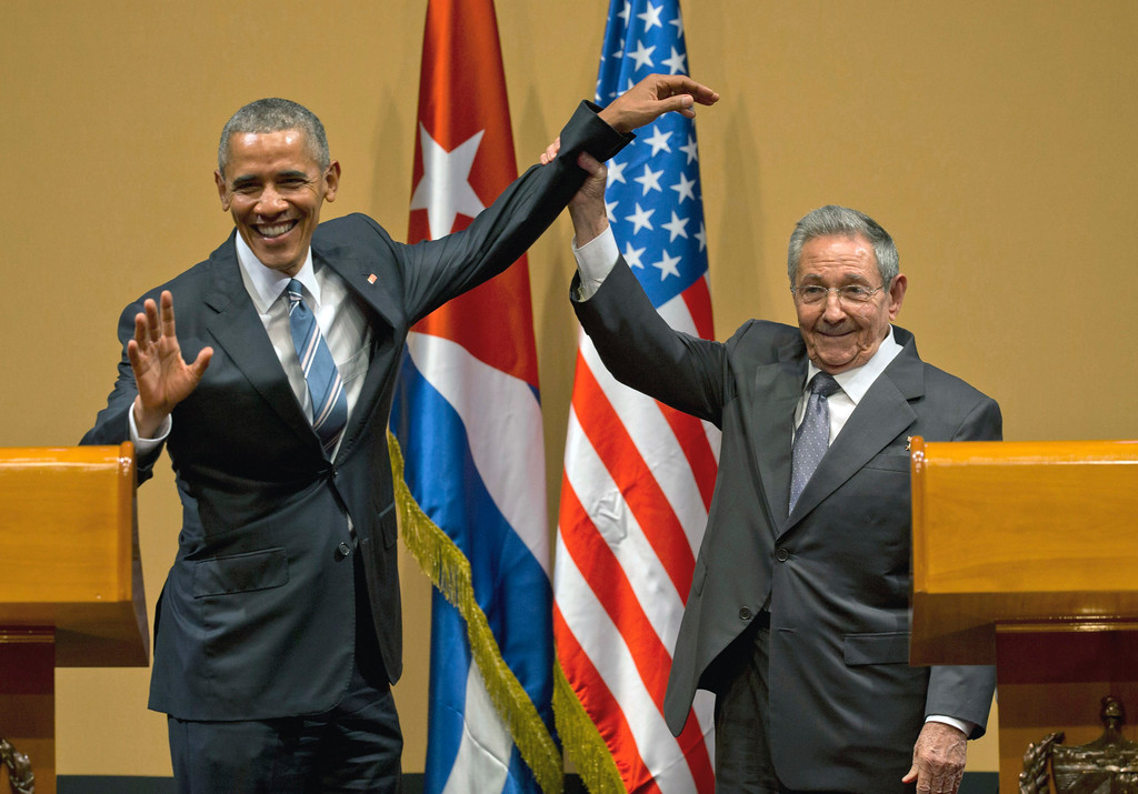 . Cuban President Raul Castro, right,  lifts up the arm of President Barack Obama at the conclusion of their joint news conference at the Palace of the Revolution, Monday, March 21, 2016, in Havana, Cuba. (AP Photo/Ramon Espinosa)