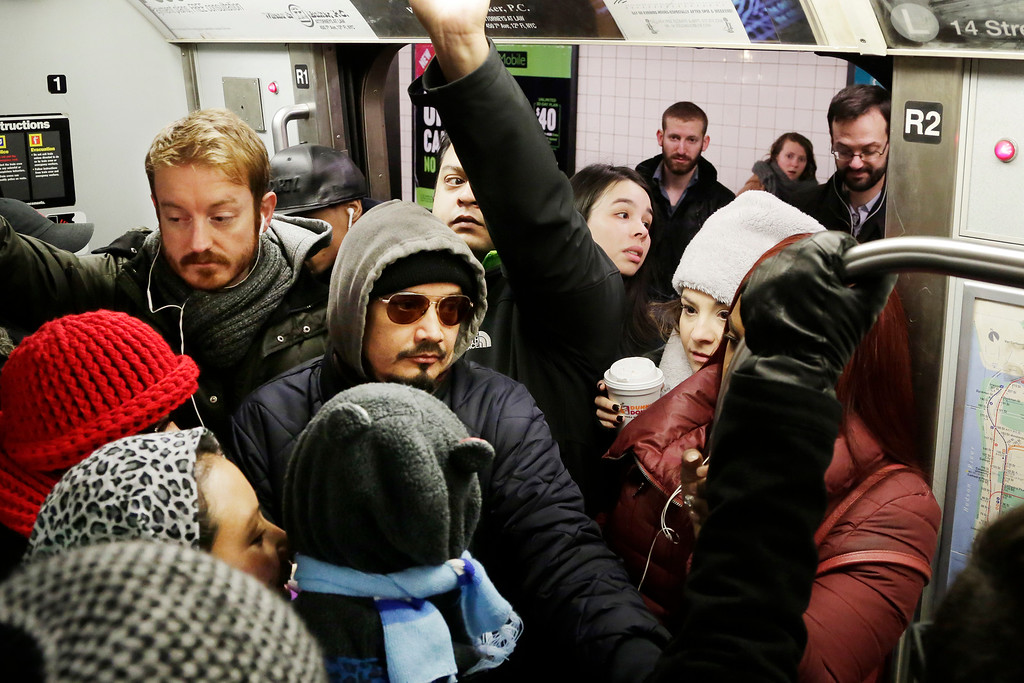 . Commuters, upper right, try to push onto a crowded L subway train, Monday, Jan. 25, 2016, in the Brooklyn borough of New York. East Coast residents who made the most of a paralyzing weekend blizzard trudged into the workweek Monday amid slippery roads, spotty transit service and mounds of snow that buried cars and blocked sidewalk entrances. (AP Photo/Mark Lennihan)