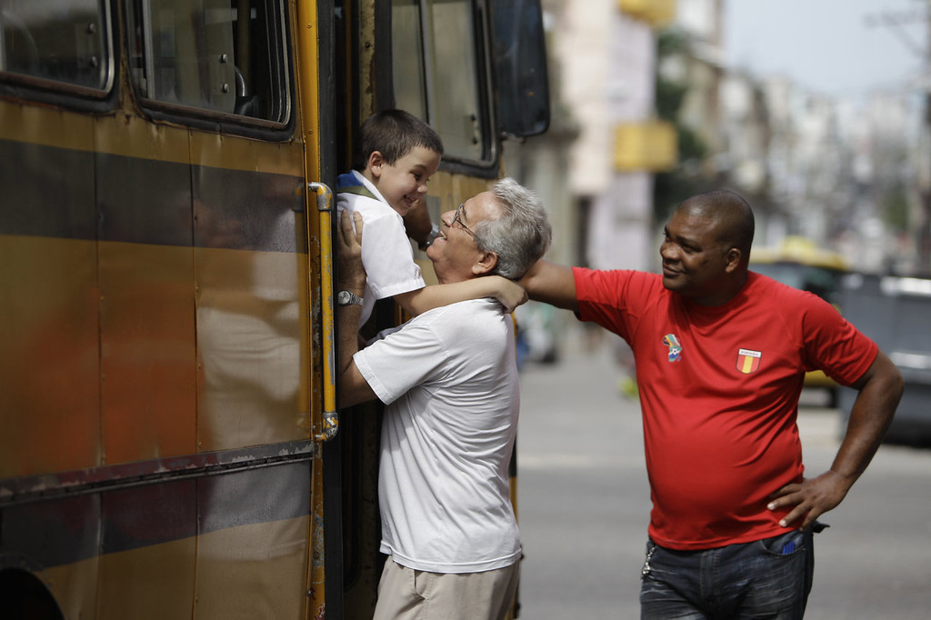 . Cristian Vazquez falls into the arms of his grandfather Francisco Vazquez as he gets off the school bus after a school day at the Dora Alonso school in Havana, Cuba on June 13, 2013. Six-year-old Vazquez was diagnosed with autism in 2008 and began attending this special school that caters to the education of children with autism. Although Vazquez\'s education is paid for by the state, his parents say that it is difficult to acquire special materials for their son, like books that have figures, colors and pictograms. (AP Photo/Franklin Reyes)